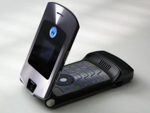 A cell phone, the original Motorola RAZR, sits on a white table flipped halfway open exposing numerical keypad.
