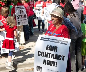 """A photograph of a teacher protesting in a crowd, with a large, square sign around her neck reading """"Fair Contract Now!�"""
