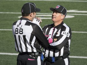 A photograph of two referees talking on a football field. Both are wearing black and white striped shirts and black hats. One is standing with their back to the camera, and the other is facing the other referee toward the camera.