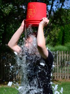 A photograph of a person standing outside, holding a red bucket upside down above their head. Out of the bucket, water and ice is falling on the person, obscuring their face and upper torso.