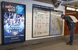 """A photograph of a wall in a subway in New York. The left side of the wall features a vertical, rectangular television screen showing an advertisement for NCAA March Madness. The right side of the wall features a large bulletin board labeled """"Customer Information Center,� showing two different maps. A person with a backpack is to the right of the bulletin board, bent over reading the map."""