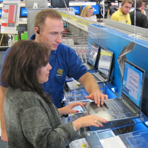 A photograph of a Best Buy employee showing a customer a computer. The employee and customer are standing in front of a computer on a display, with the employee showing the customer a page on the laptop. In the background is the rest of the Best Buy store, with other customers and employees.