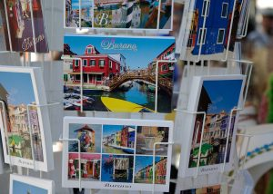 A photograph of a postcard rack, with seven different types of postcards on it. Each postcard shows different scenery. The main postcard in focus in the middle of the picture. It shows a red building to the left with a bridge over water to another building to the right, with a yellow boat in the foreground.
