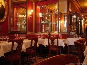 A photograph of the inside of Le Procope. Four tables with white tablecloths are in the foreground, with wooden chairs around them. Behind them on the wall are mirrors and a display of glasses.