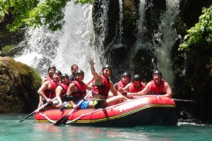 A photograph of nine people in helmets and lifejackets, sitting in a raft in the water. The person in front has their hand raised in a wave toward the camera. In the background is a waterfall and greenery.