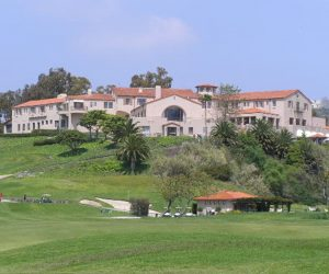 A photograph of a very large, two-story Spanish style mansion on top of a hill, with trees in the background and in front of the mansion. Another smaller house with a red roof sits at the bottom of the hill.