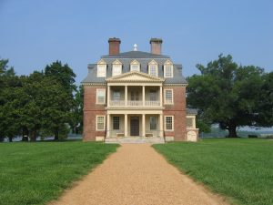A photograph of the Shirley Plantation, shown from the front with a path leading up to the house. The house is three stories tall, with five windows on each story. A porch on the front of the house is two stories high. Trees are lined up on either side of the house, with a blue sky in the background.