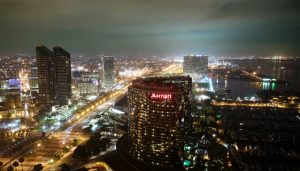 A photograph of the San Diego cityscape at night, lit up with lights. The San Diego Marriott in the foreground, a large, arch shaped skyscraper. Water is to the right of the Marriott, with lighted docks extending into the water. A highway is to the left, lined with streetlights. Other buildings are in the background, including two other skyscrapers to the left and two in the distance.