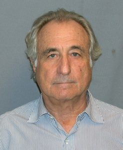 A photograph of Bernie Madoff standing in front of a blue background.