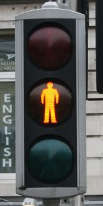 A photograph of a stoplight, with the silhouette of a person lit up in the center, yellow light.