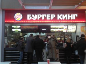 Photograph of the inside of a Burger King restaurant, with people standing in line to order. The Burger King store name is in Russian.