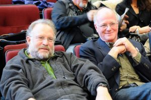 A close up photograph of Ben Cohen (right) and Jerry Greenfield (left) sitting in stadium style theater seats, with people sitting around them.