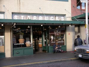 A photograph of the storefront of the first Starbucks store with iconic green awning viewed from a street.