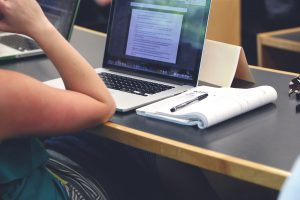 A photograph of a person sitting at a table with their laptop open to a window filled with text. A notebook is open beside the laptop with a pen on top.