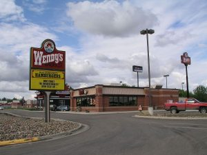 A photograph of a Wendy's Restaurant, rectangular building with a flat roof, viewed from the road. Pole mounted Wendy's sign in front.