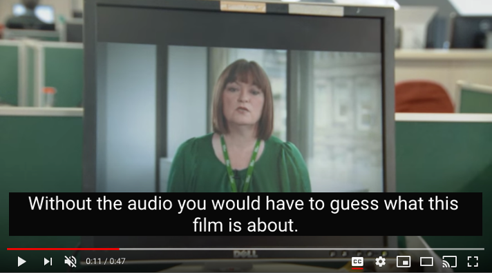 """A screenshot of a youtube video showing a woman in a green shirt speaking. A black box with text on the video says, """"Without the audio you would have to guess what this film is about""""."""